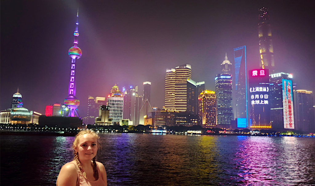 Zoe stood on The Bund in Shanghai with high rise buildings illuminated at night on the other side of the river
