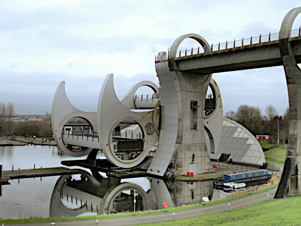 The Falkirk Wheel, a rotating boat lift, is shown mid-rotation. The lake next to it is very still and there are very few people around.