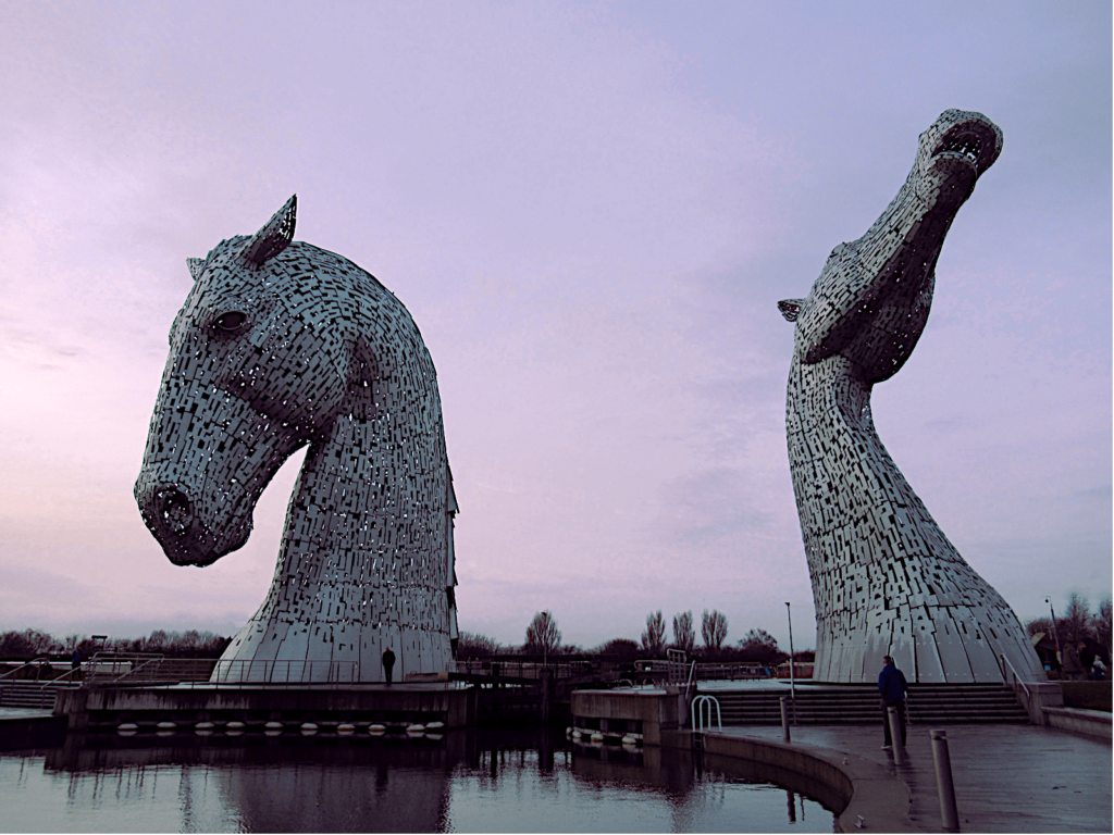 The two Kelpie heads in Falkirk are shown against a purple and pink dusk skyline.