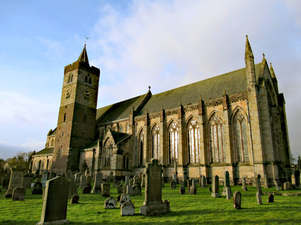 Showing Dunblane Cathedral from the side. Tombstones are shown in the grounds of the church in the foreground of the picture. The cathedral dominates the picture with stunning brickwork and stained glass windows. A clock tower is visible on the left side of the church.