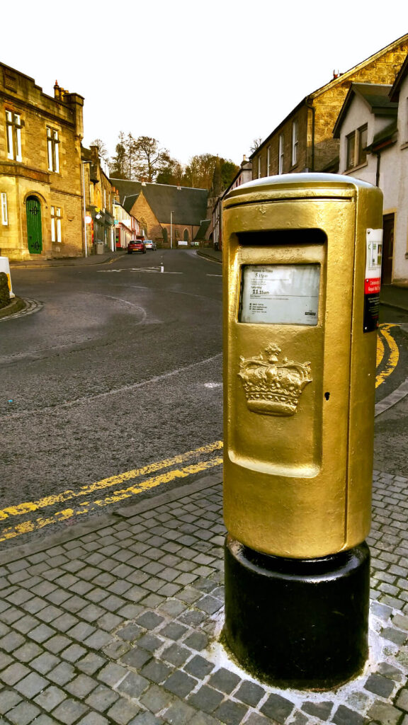 Golden post box. Painted in 2012 by Royal Mail to celebrate Andy Murray's Olympic Gold Medal in the Tennis Men's Singles. It is shown with houses and shops in the background on a quiet street.