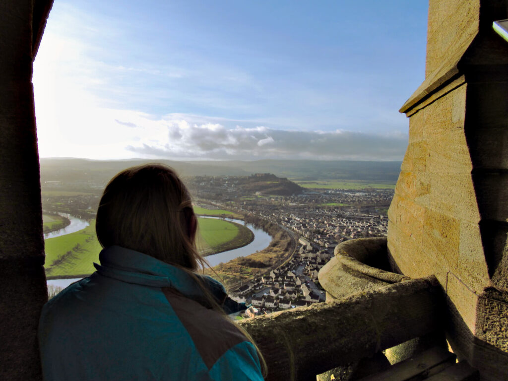 Zoe looking out over Stirling and Stirling Castle from the lookout at the top of the Wallace Monument. The sun has just risen, the light is golden and the sky is mainly blue with some clouds in the distance.