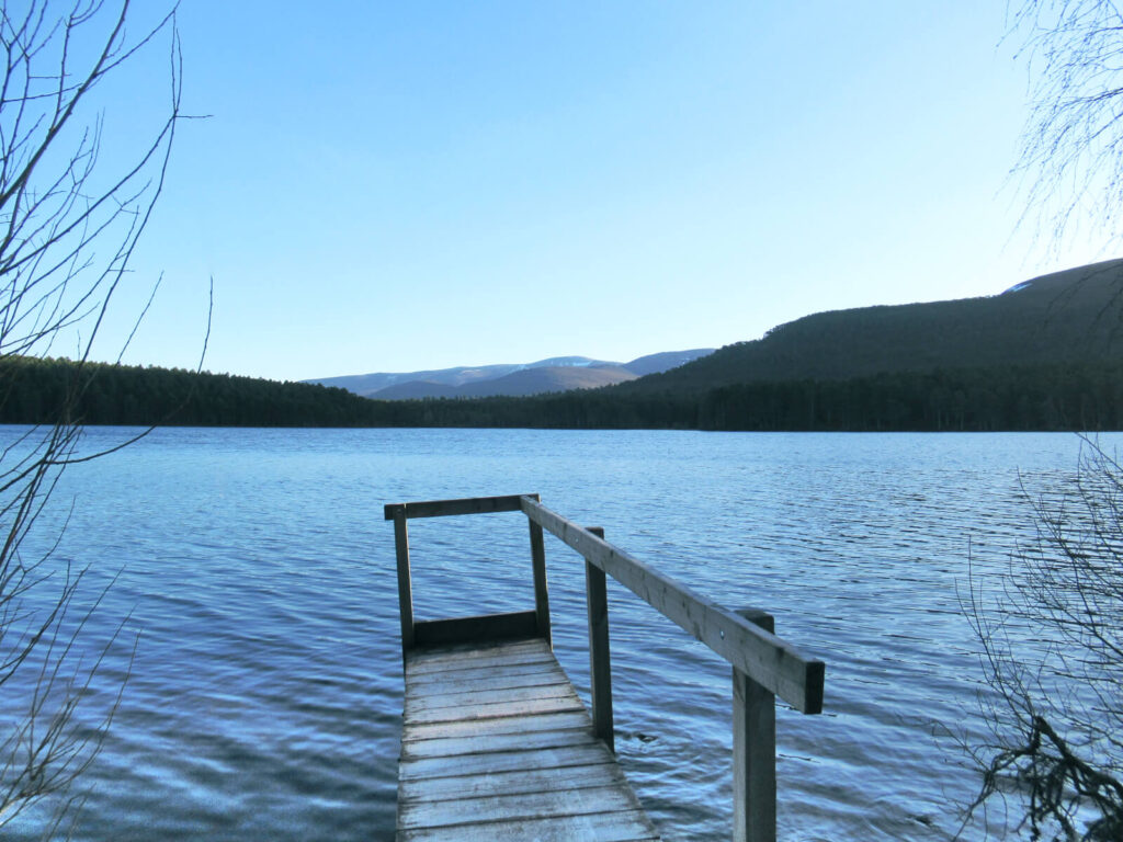 A small jetty extends into the loch, which is a rich blue colour and slightly wavy. There are wooded mountains in the background with a small layer of snow at the top. The sky is crisp blue