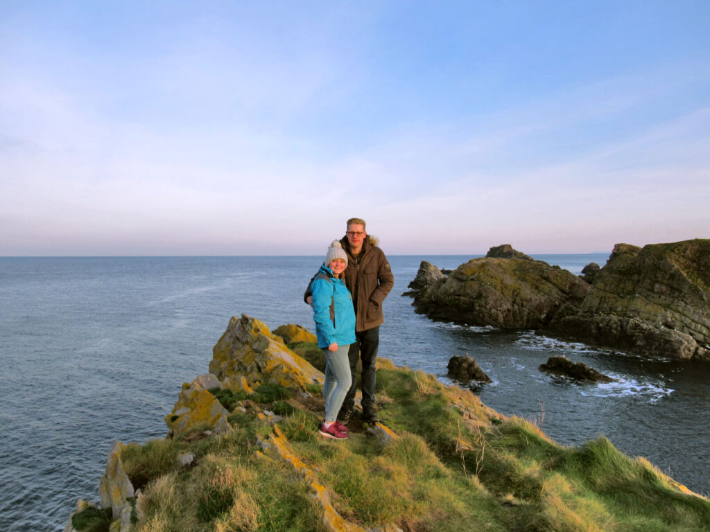 Zoe and boy-Zoe stood on a cliff top overlooking the Moray Firth. It's just before sunset and there are pink tinges to the sky on the horizon. Waves crash against the rocks that stick out from the sea just away from the coast line.
