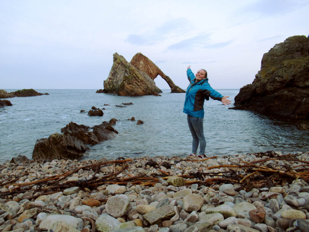 Bow Fiddle Rock is shown in the distance. Zoe is stood on the pebble beach, arms outstretched smiling at the camera.