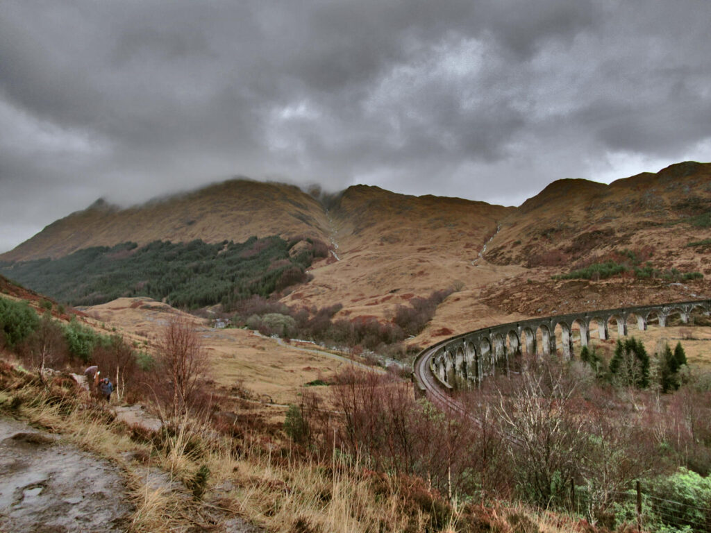Dark grey clouds hang low on the hilltops behind the Glenfinnan Viaduct. The curve of the viaduct is on the right hand side of the picture and looks small in comparison to the surrounding hills.