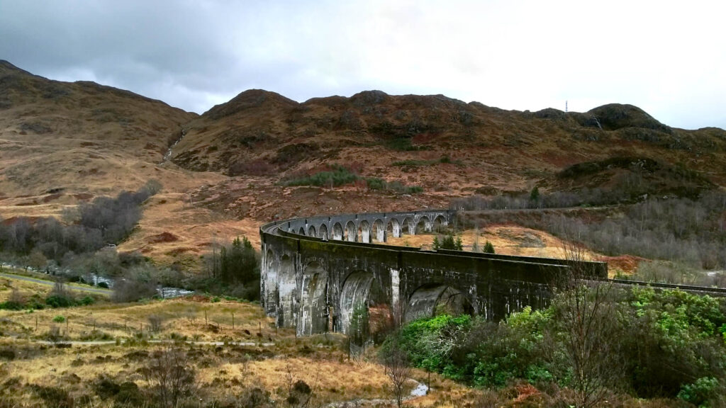 The curve of the Glenfinnan Viaduct is visible against the brown hills of Scotland and the grey skies