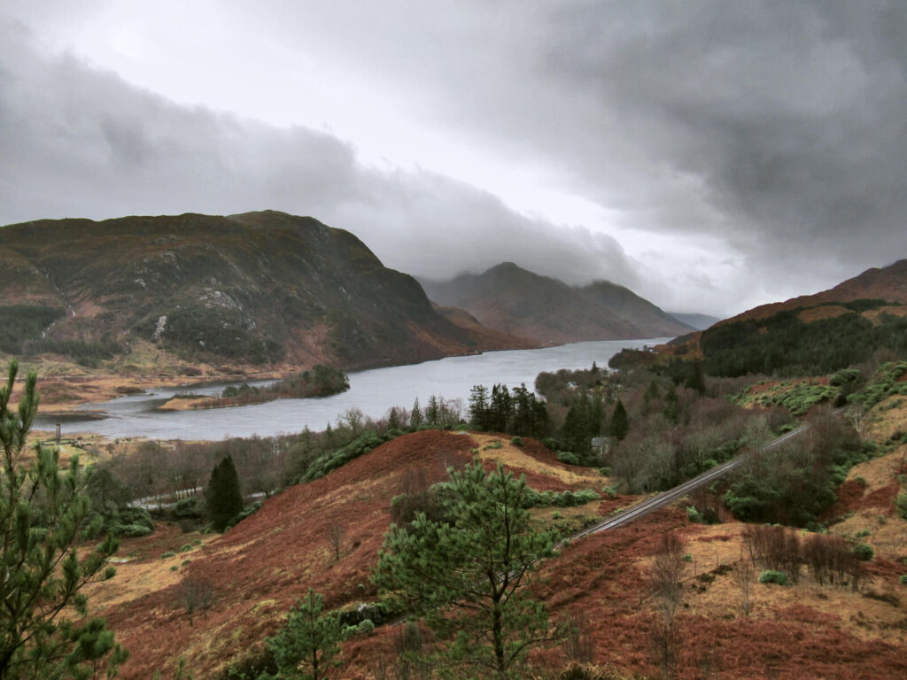 Clouds hang low over the hills and mountains surrounding Loch Shiel. The brown and red earth contrasts against the grey sky.