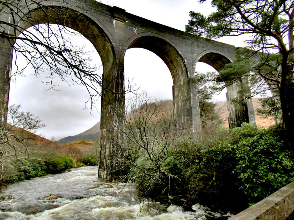 A river flows rapidly underneath the grey arches of the viaduct. Grey clouds can still be seen in the distant sky.