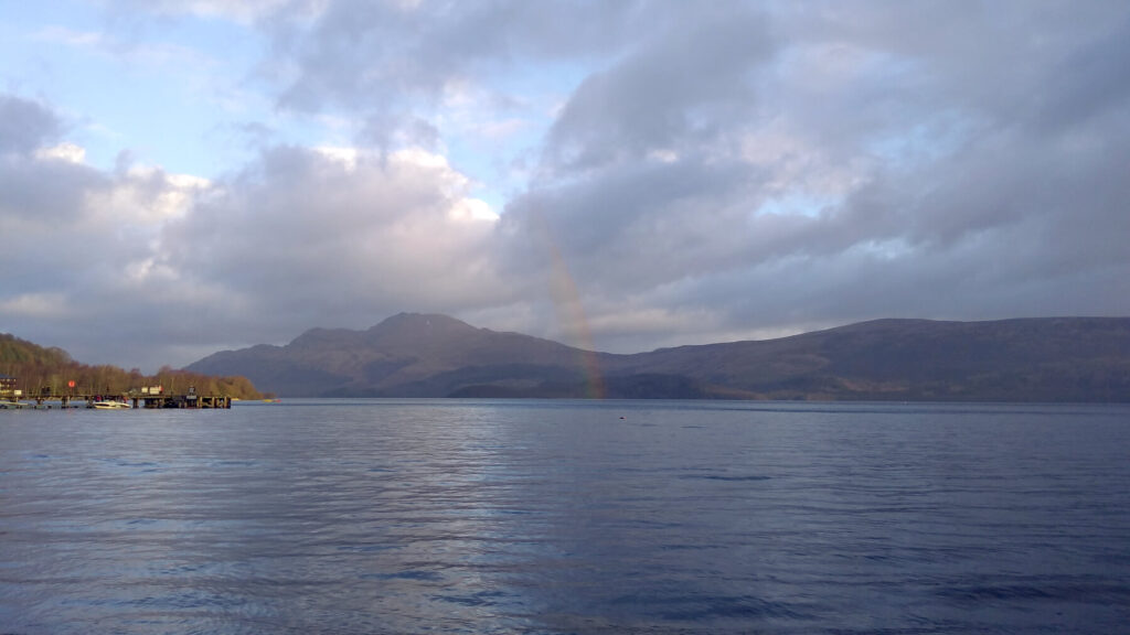 A rainbow emerges out of Loch Lomond and up into the clouds. It is a cloudy day but the sun is out. The hills on the opposite side of Loch Lomond can be seen.