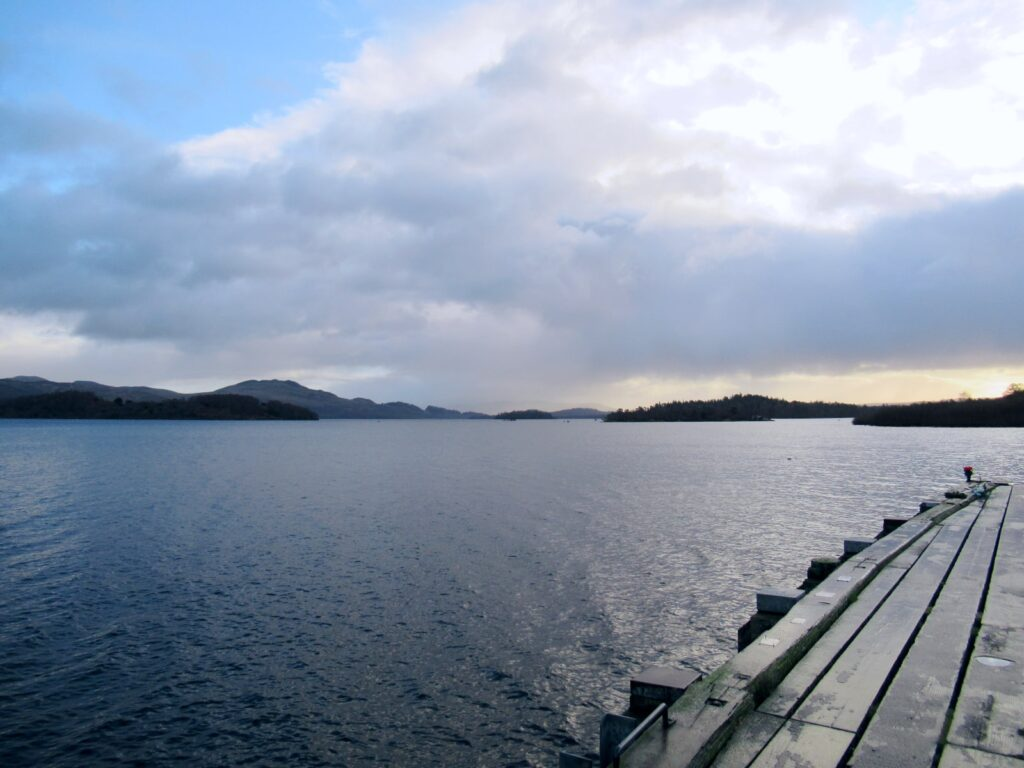A cloudy day at Loch Lomond. The edge of a wooden jetty can be seen in the picture foreground and the water continues into the horizon. Small islands can be seen.