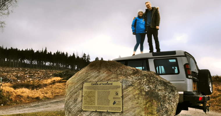 Two people stood on the roof of a car, in front of the car is a large rock. The rock is marked with a plaque that says 'Centre of Scotland'. A row of trees is visible in the background and pink and blue tones can be seen in the cloudy sky