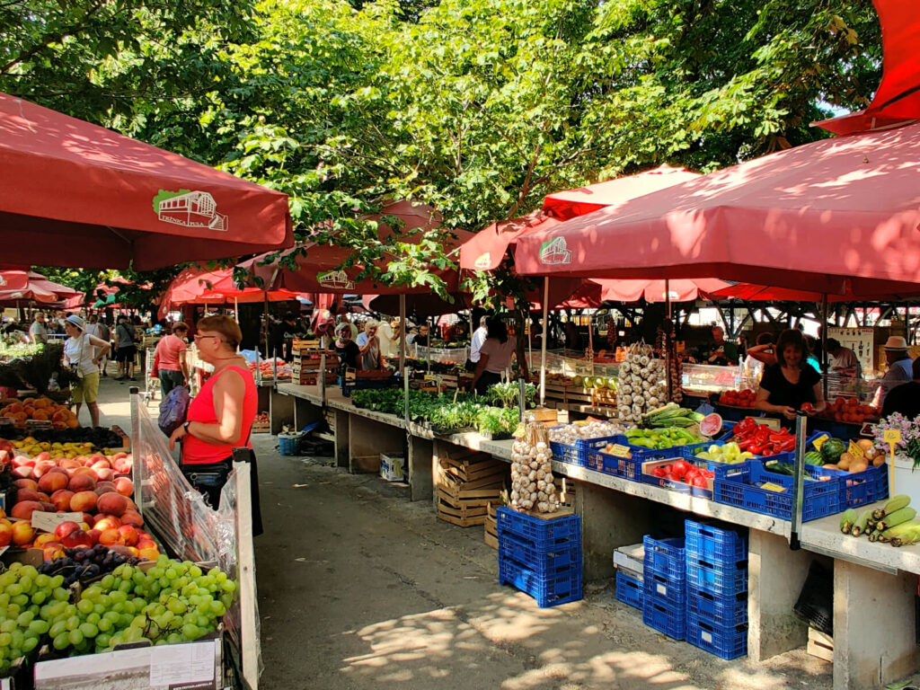 The photo shows a market scene, the stalls run in parallel lines and are sheltered by red covers. Fruit and vegetables of all colours are on display. Istria and Pula are worth visiting for the amazing food, with both Italian and Balkan influence!