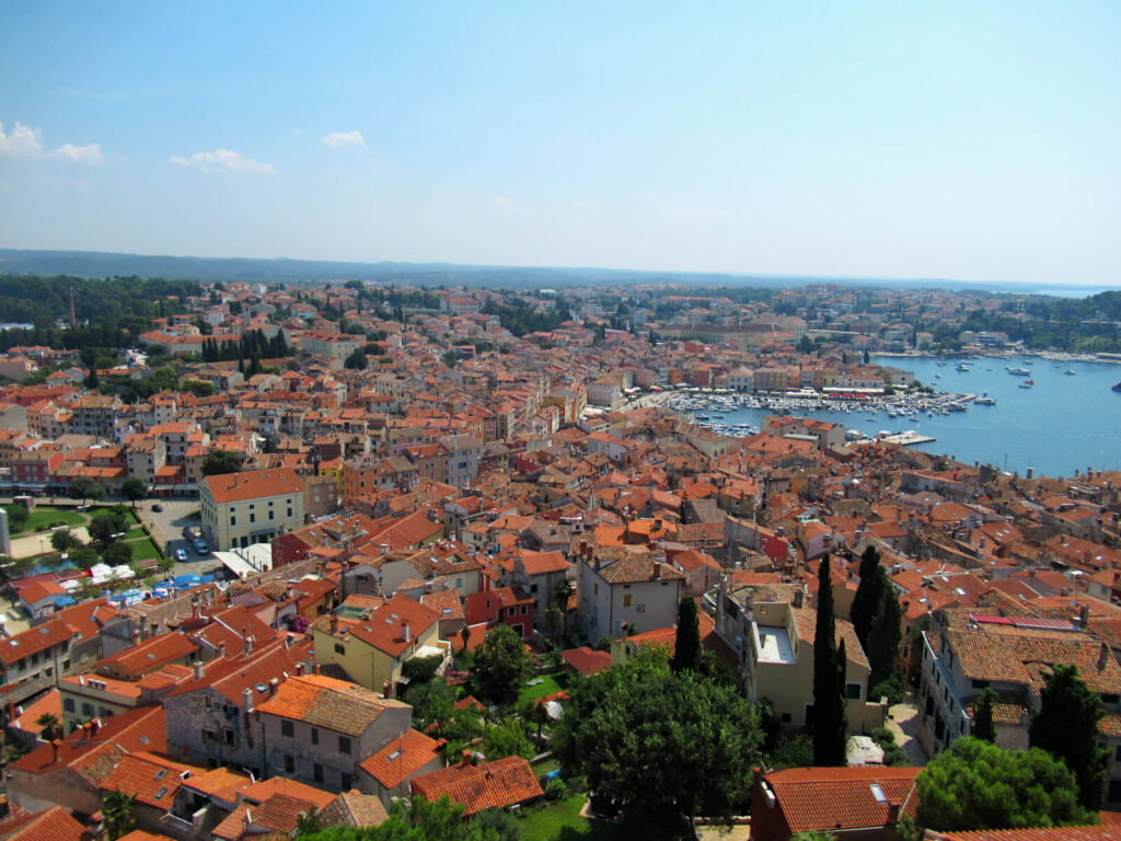 A birdseye view of Rovinj from the top of the bell tower. The orange roofs contrast with the blue sea and sky. Rovinj is worth visiting as a day trip from Pula to experience the feel of Venice and amazing Italian-influence food!