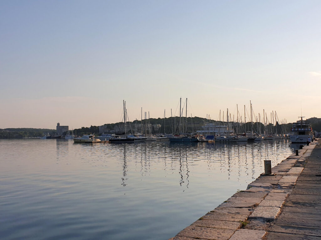 Sail boats without masts line Pula Marina. It is just after sunrise and the light is faint and soft. The water is calm and the sky is clear.