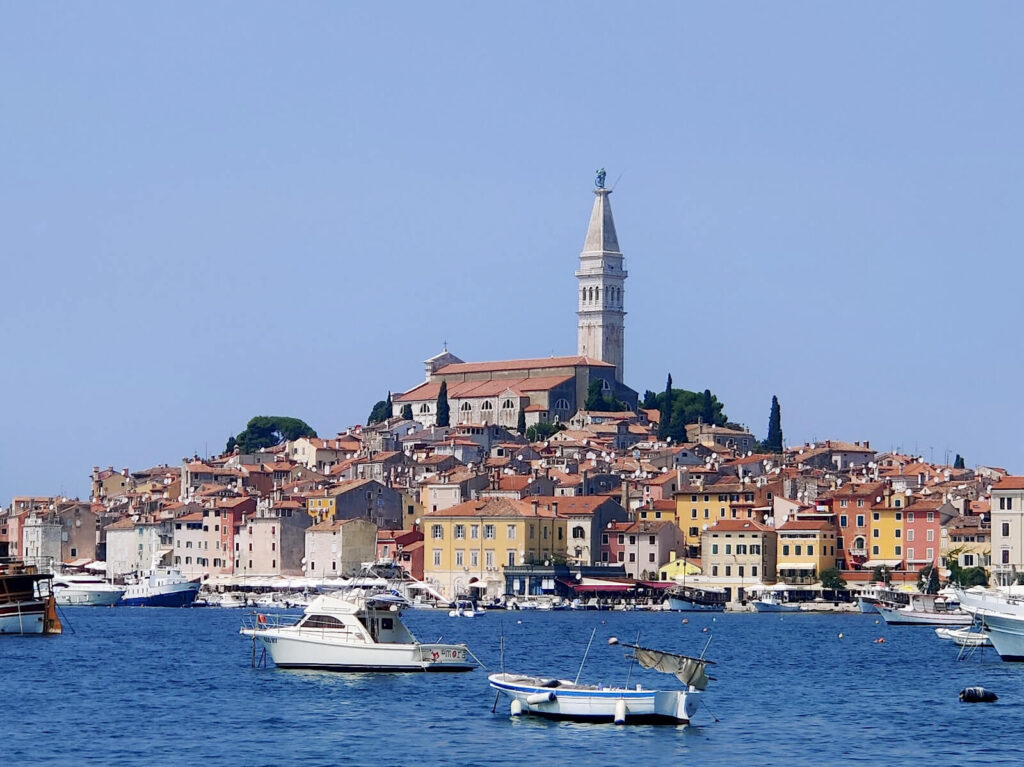 The church tower stands above the other red-roofed buildings that make up Rovinj's old town. In the foreground many boats are docked in the marina. The colourful buildings contrast with the bright blue sea. Taking a day trip here is one of the best things to do whilst in Pula!