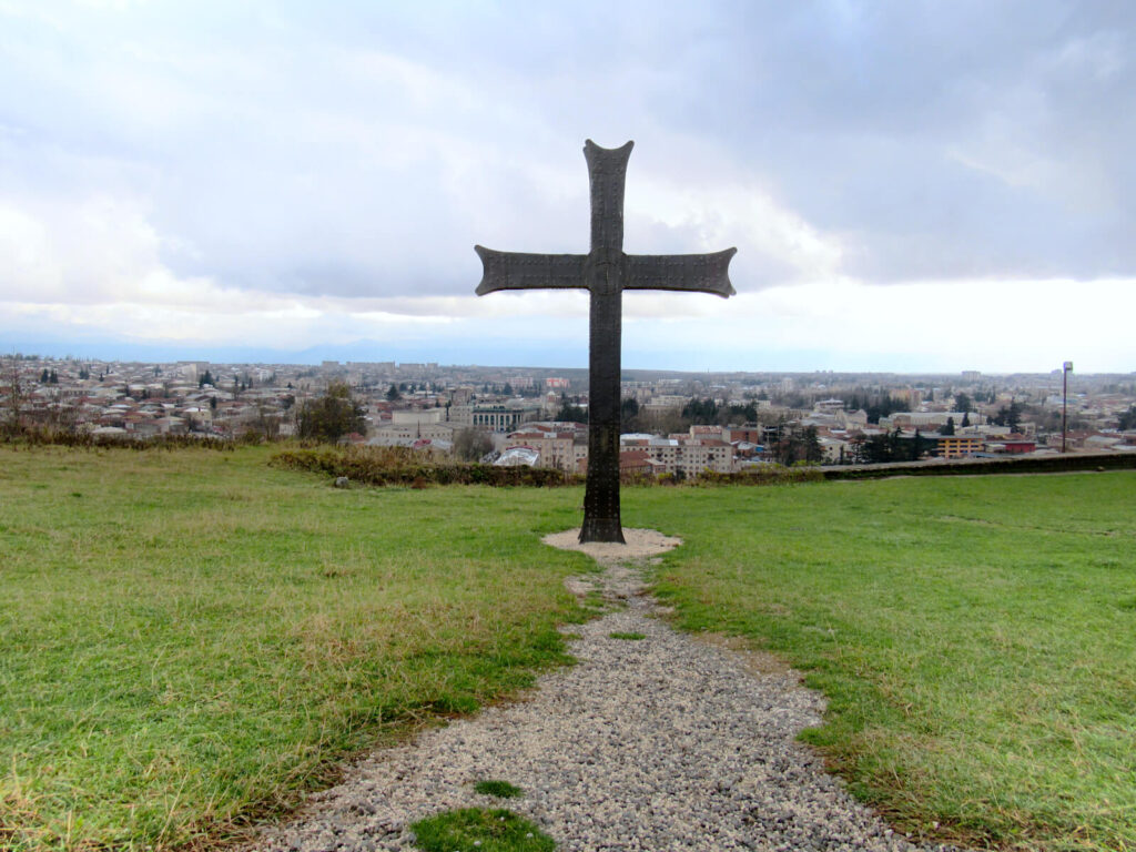 The view of Kutaisi from Bagrati Cathedral. A dark metal cross is in the forefront of the image overlooking the city.
