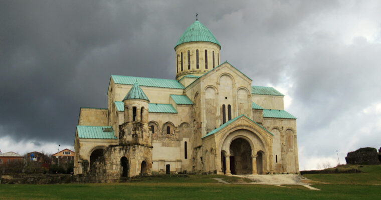 Bagrati Cathedral, with it's iconic teal green roof stands overlooking Kutaisi from the hill top. Dark rain clouds loom in the background but do not distract from the brightness of the building, which has a sandstone colour.
