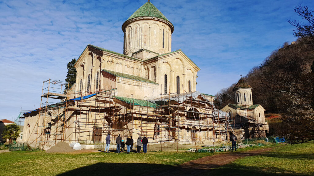 Gelati Monastery shown with scaffolding around the bottom of the building. A small group of visitors stand in front of the church admiring it's stunning medieval architecture.