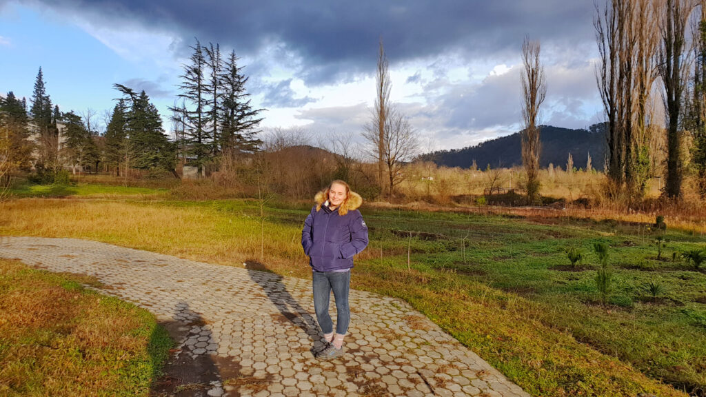 Zoe stood in Kutaisi Botanical Garden during golden hour, the light is low and warm. Winter trees are all around