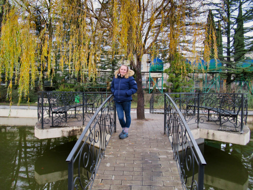 Zoe stood on a a bridge over a pond in Kutaisi Botanical Garden. A weeping willow tree hangs low with its winter yellow leaves.