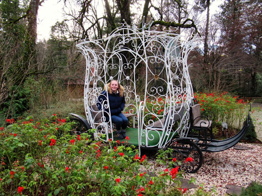Zoe sits in a sculpture of a horse-drawn cart (no horses!), smiling at the camera. Although it is winter and many trees are bare, bright red flowers surround the carriage