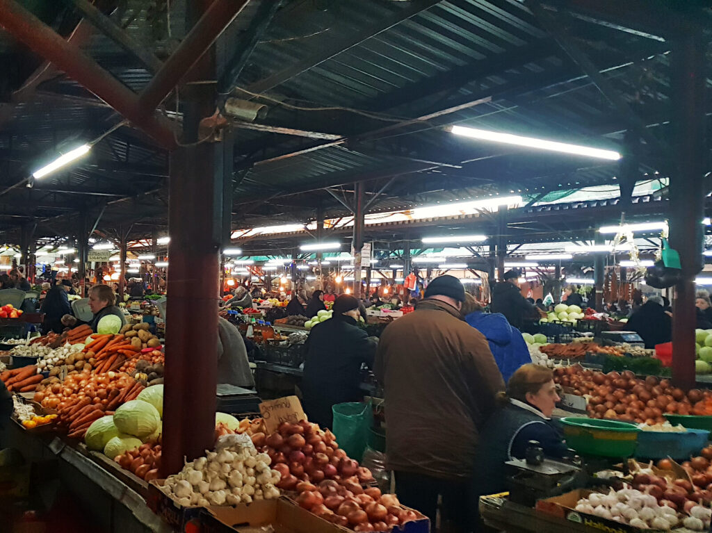Looking across a busy market. Traders sit behind their stalls and many types of fruit and vegetable are visible and piled high. The warm glow of the lights in this sheltered part of the market adds to the intimate feel