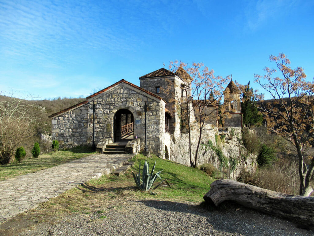 The Motsameta monastery: an old stone building set into the side of a hill surrounded by lush green land. The winter sky is clear and crisp blue.