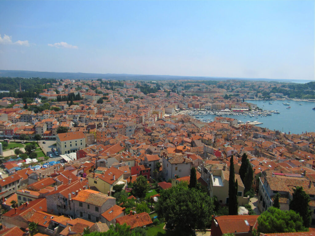 A bird's eye view of Rovinj looking south-east from the bell tower, the best views for your day trip from Pula to Rovinj. Orange roofs, the marina and hills in the distance can all be seen
