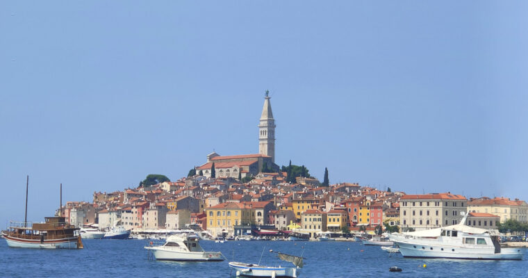 The beautiful old town of Rovinj with brightly coloured buildings and the church and bell tower rising out the top. Boats in the marina are in the foreground. A great photo spot if you're visiting from Pula to Rovinj