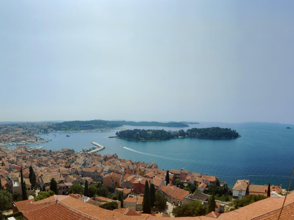 View of the Adriatic Sea and southern Rovinj from the Bell Tower. The orange roofs of the town can be seen in the foreground and a small island sits in the middle of the sea in the centre of the photo.