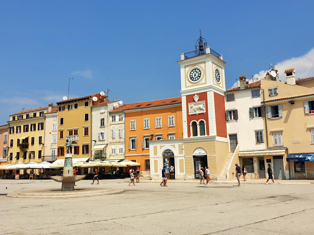 The square in the centre of Rovinj. There is a large open space iwth a statue in the middle, surrounded by buildings that are orange, yellow and beige.