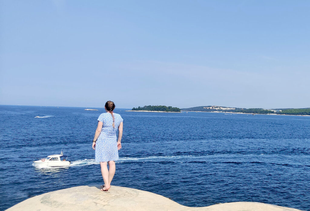 Zoe stood on top of an abandoned bunker looking out over the dark blue sea. Zoe is wearing a light blue and white dress with flip flops.