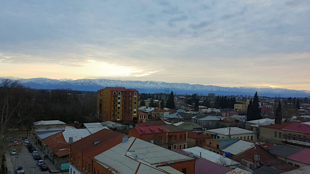 Looking south from Kutaisi towards the snowy mountains at sunset. The sun has just dipped below the mountains and the sky has a yellow tint. In the foreground the 1970s style buildings of Kutaisi can be seen