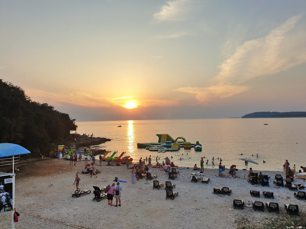 Ambrela Beach at sunset, people are dotted across the beach and shallow sea. The sun is golden and just above the horizon. One of the best beaches in Pula