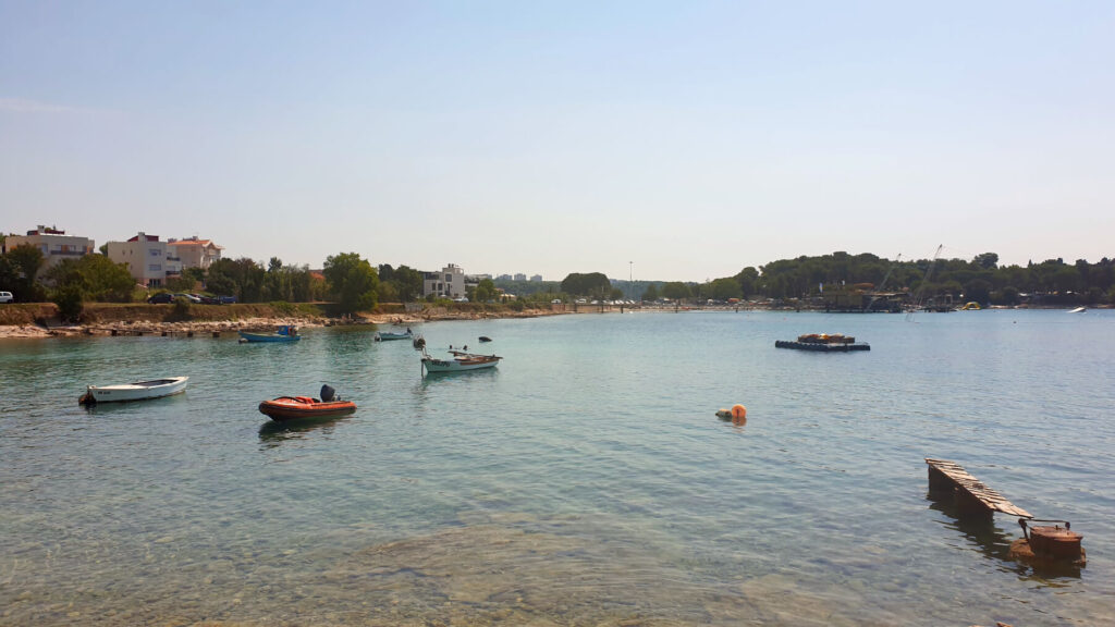 Panoramic shot of Valovine Beach with dingy boats anchored in the shallow, clear waters of the bay.