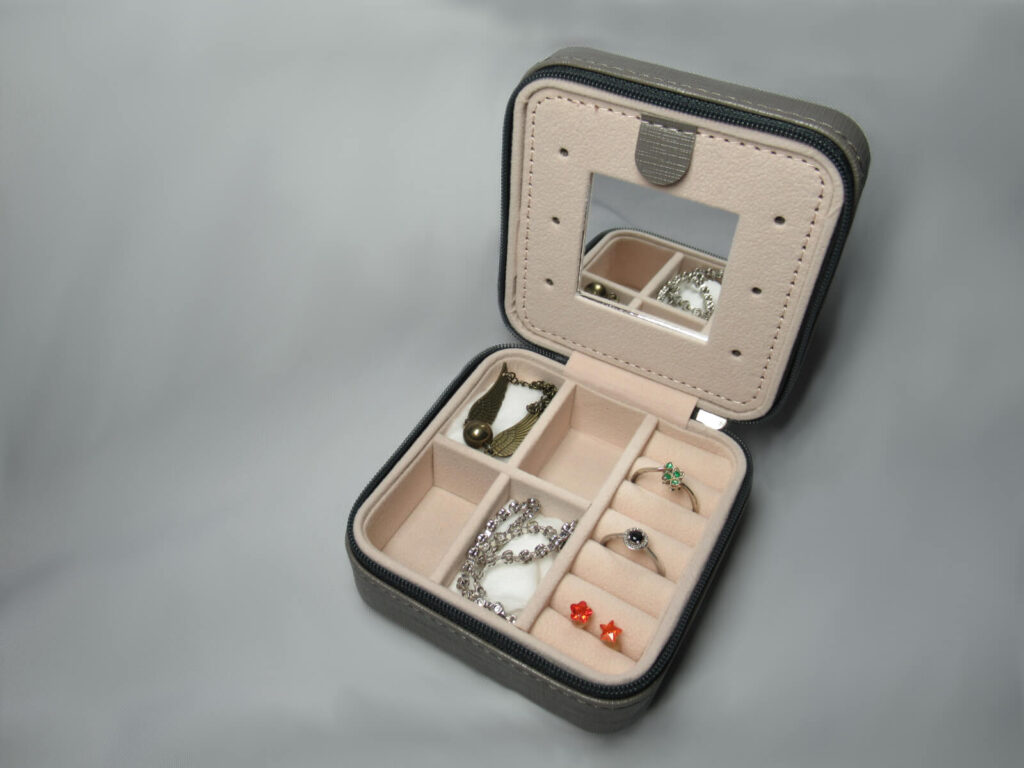 Small travel jewellery box shown containing a small mirror, two rings and a pair of ear rings in narrow cushioned partitions. Two bracelets are shown in a separate partition. Take inspiration for unique travel gifts!