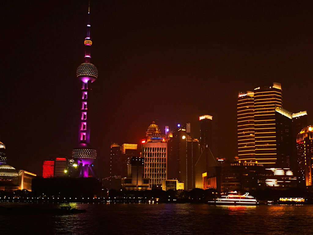 View of the Shanghai TV Tower from the Bund at night. The TV Tower is illuminated with pink and yellow lights against the dark of the night sky. A must see in a shanghai 3-day itinerary