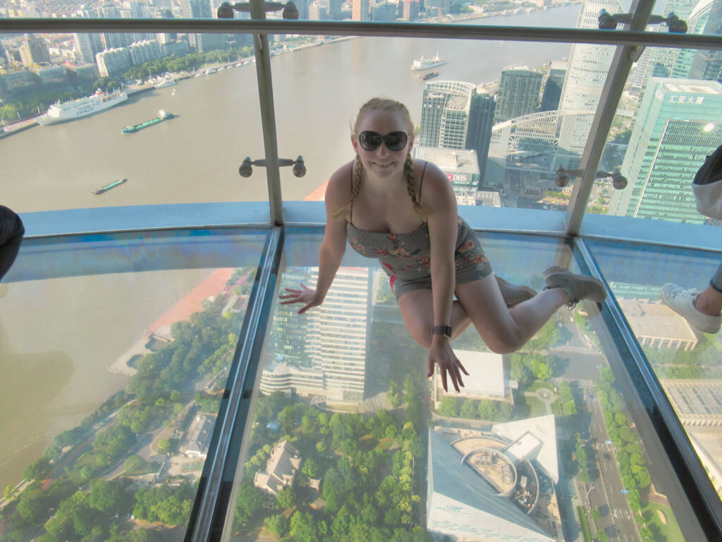 Zoe sat on the 360 transparent skydeck of the Shanghai TV Tower - 259 metres above the ground! Face your fears with this Shanghai 3-day itinerary!