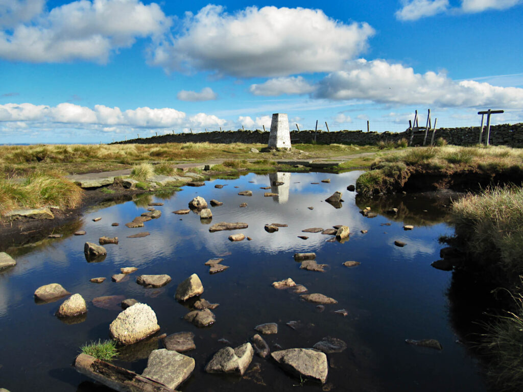 A beautiful day on the summit of Buckden Pike, blue sky and fluffy clouds. The reflection of the trig point in the puddle adds to the calm atmosphere