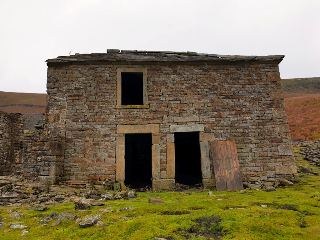 An abandoned farmhouse with two front doors and an upstairs window - very dark inside. The brickwork stands strong after years on the exposed Yorkshire Dales hillside - would you go inside?