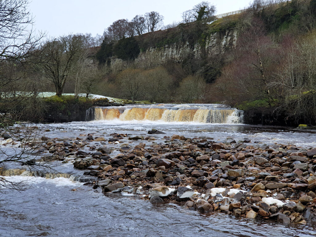 A highlight of this Yorkshire Dales waterfalls walk is Wain Wath Force, a low but wide waterfall under the shadow of rocky cliffs