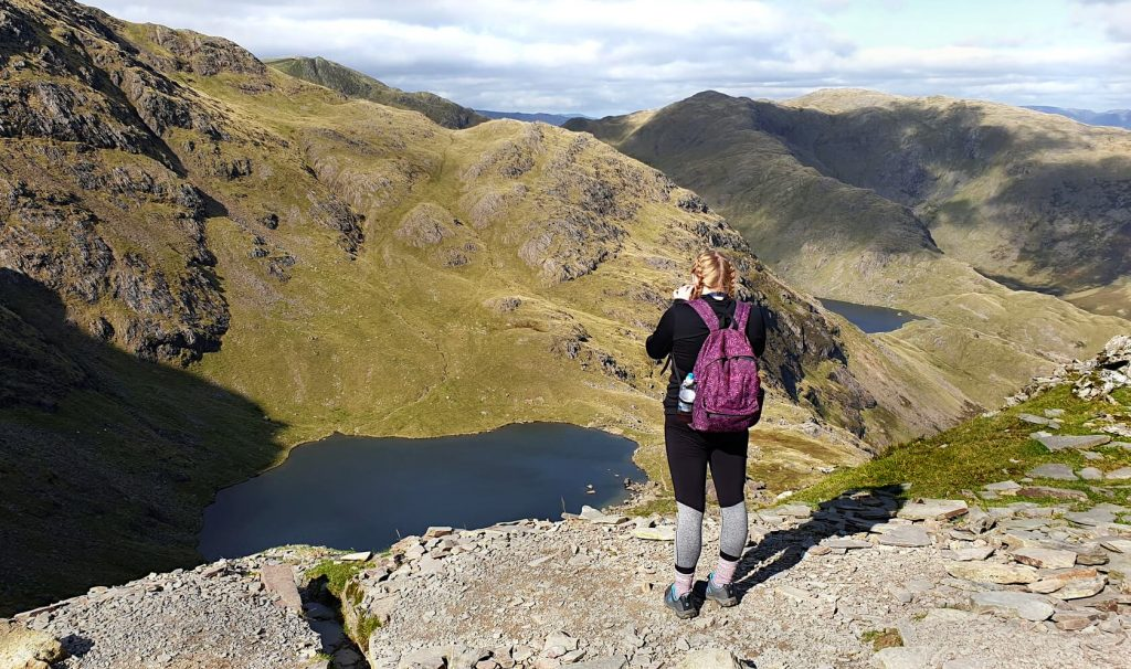 Zoe stood taking a photo of Low Water from the eastern side of the Old Man of Coniston.