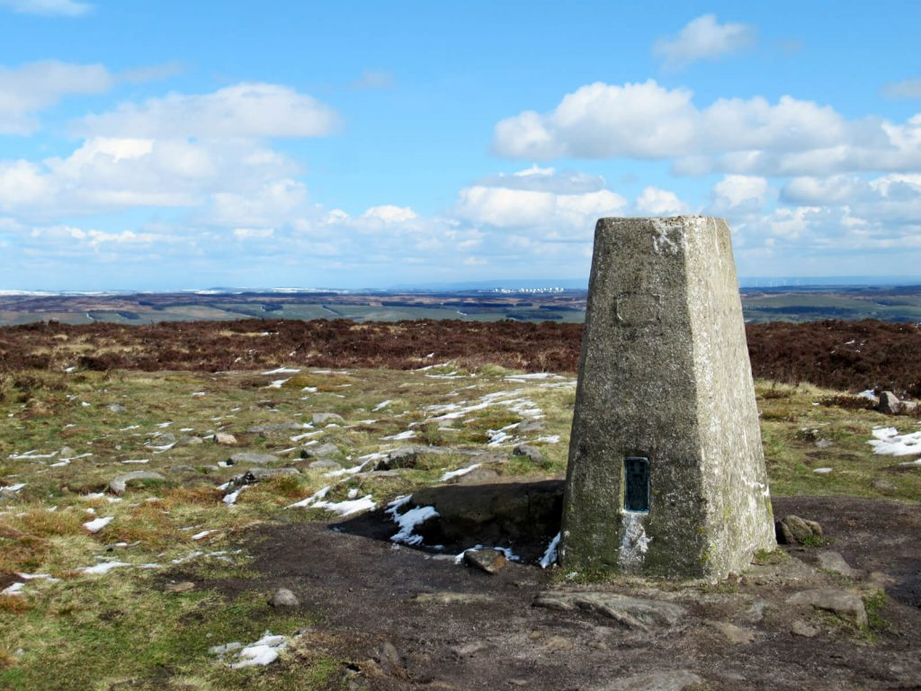 The highest point of Ilkley Moor - marked with a concrete trig point and overlooking the Yorkshire hills