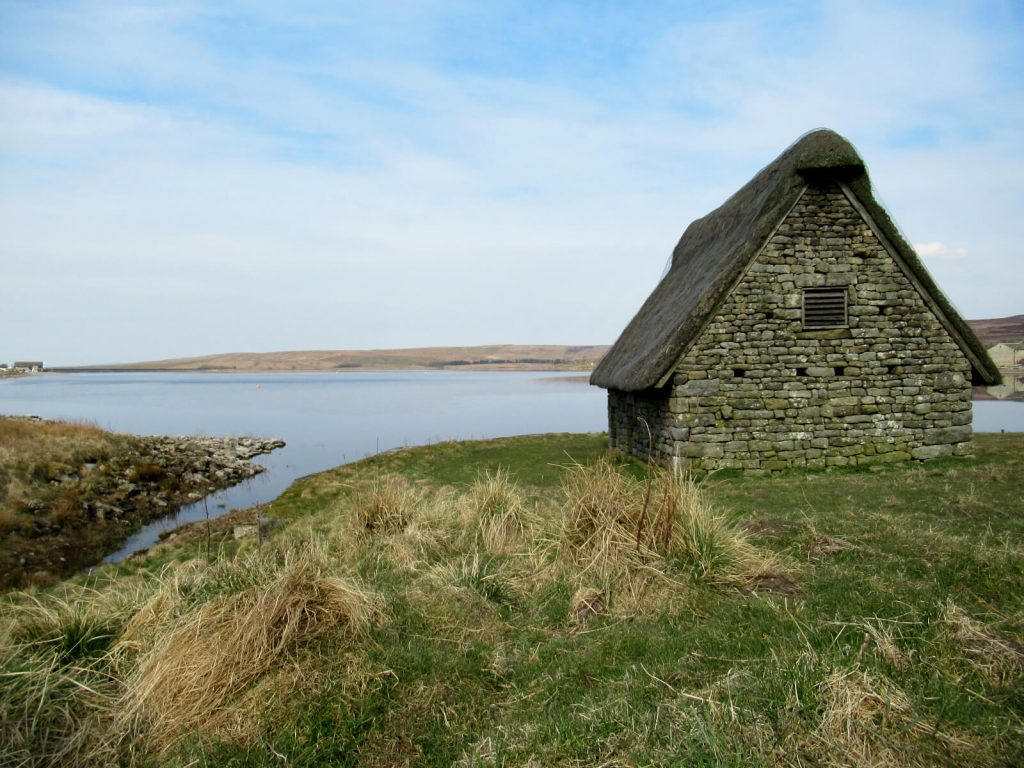 The restored medieval barn on the eastern shore of Grimwith Reservoir. The walking route takes you behind here and the holiday cottages