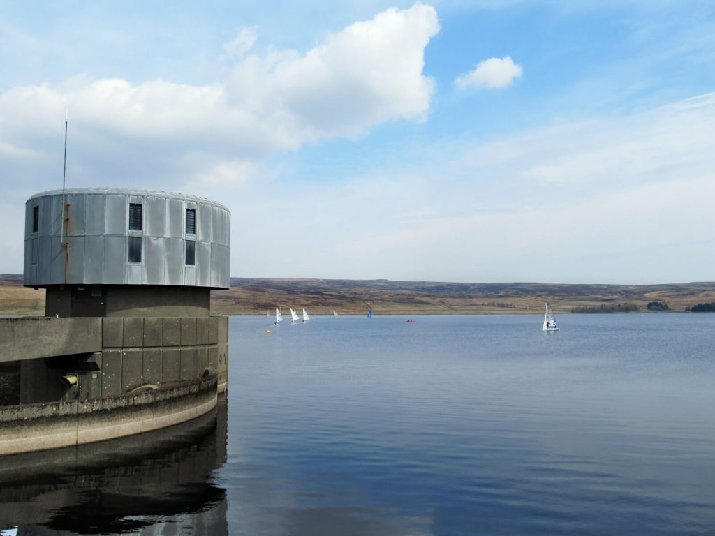 Sailing boats on grimwith reservoir with the watch tower in the foreground
