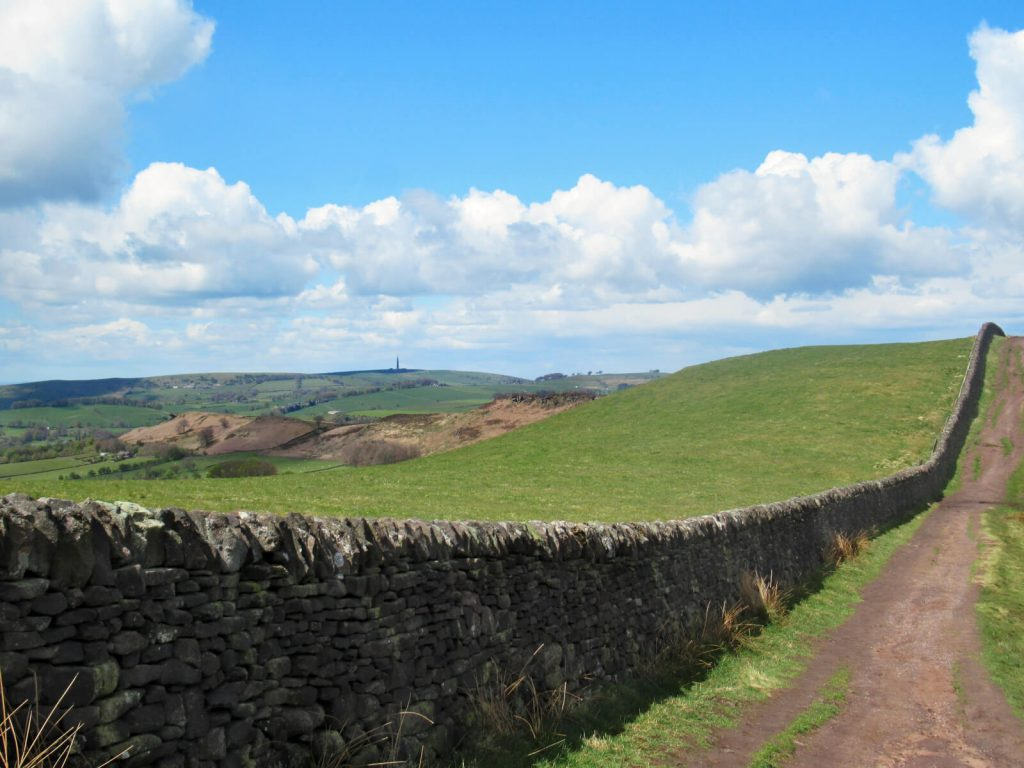 The rolling hills of the Staffordshire Peak District. Walk along the path as it follows the drystone wall to Lud's Church.