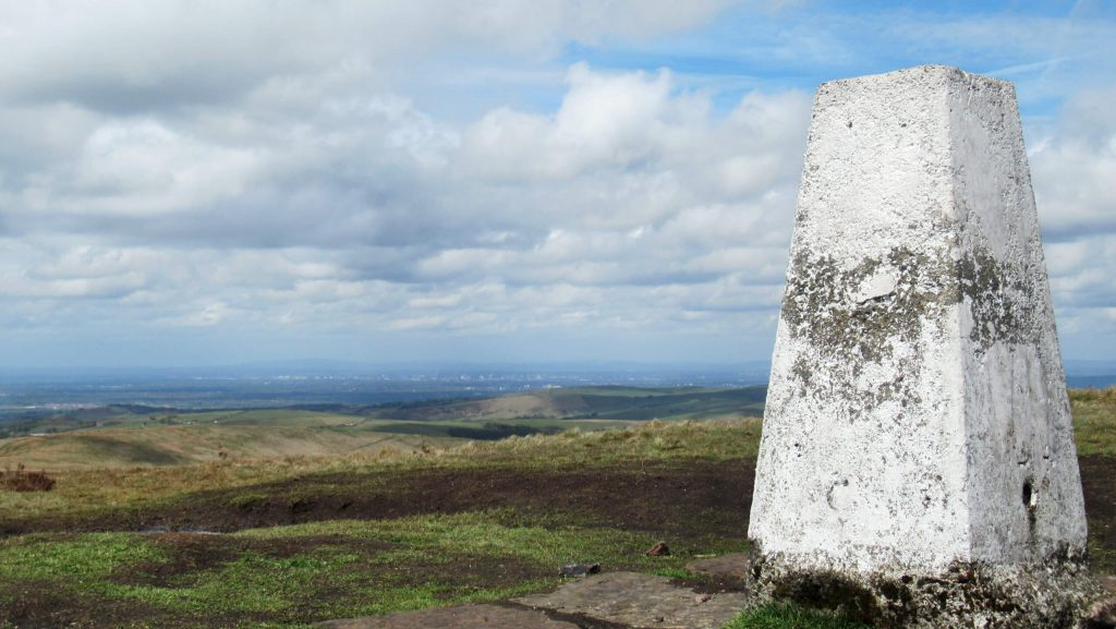 Looking north-west from the top of Shining Tor with Manchester in the background and the trig point in the foreground