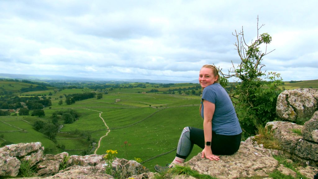 Zoe sat on top of Malham Cove looking out over the Yorkshire Dales