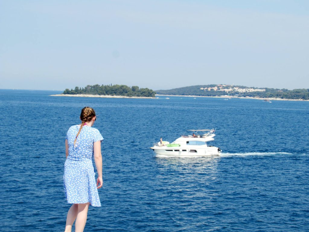 Zoe stood in a blue and white dress facing away from the camera and looking out to sea. A small, white yacht is passing by surrounded by the dark blue sea. In the background a small island with lots of trees is visible. The sky is blue and there are no clouds in sight! One of the best things to do in Pula is to take a trip to Rovinj!
